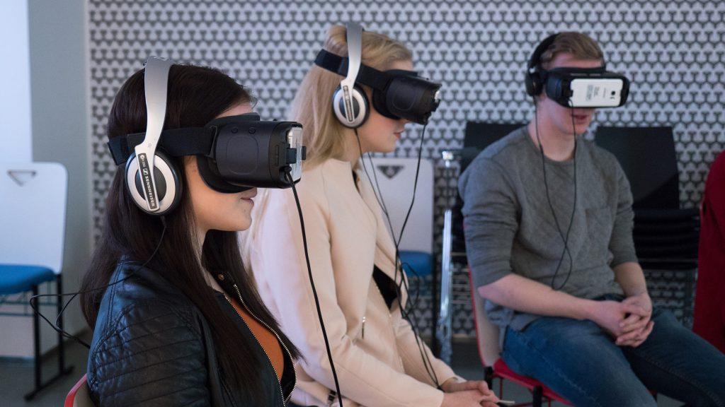 Kaksi tyttöä ja poika istuvat, kaikilla on kuulokkeet ja VR-lasit.