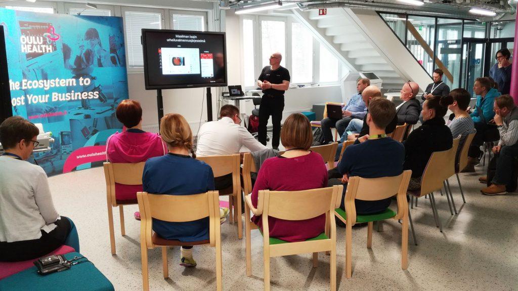 """Miehiä ja naisia istuu tuoleilla kuuntelemassa miestä, joka seisoo tilan etuosassa esittelemässä. Taustalla mainos """"Oulu Health, the ecosystem to boost your business."""""""