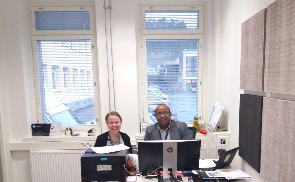 Hymyilevä nainen ja mies istuvat työhuoneessa rinnatusten tietokoneen äärellä, taustalla ikkuna ja pihamaisemaa.