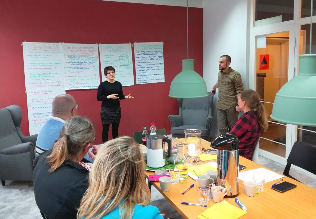 Työpaja, nainen esiintymässä, vieressä seisoo mies. Pöydän ympärillä ihmiset kuuntelevat. Punainen taustaseinä, seinällä fläppipapereita täynnä tekstiä.