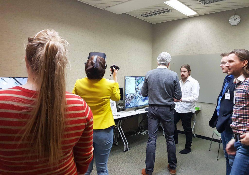 Miehiä ja naisia seminaaritilassa, keskustelua, yksi käyttää virtuaalilaseja.