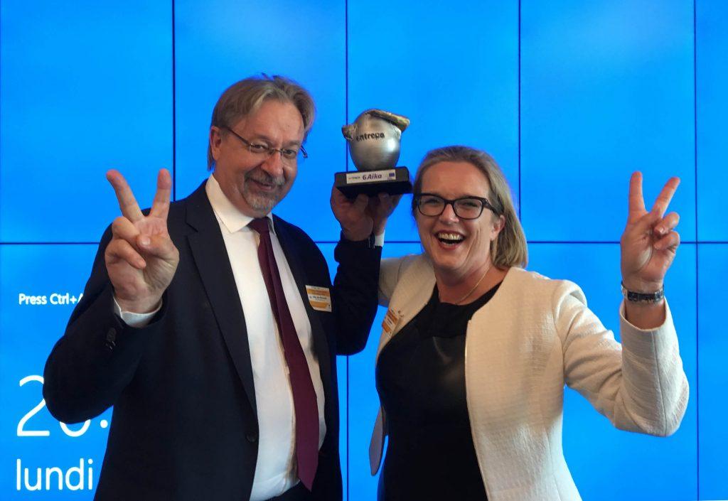 Mies ja nainen palkinnon kanssa, näyttävät voitonmerkkiä. Iloinen tunnelma.
