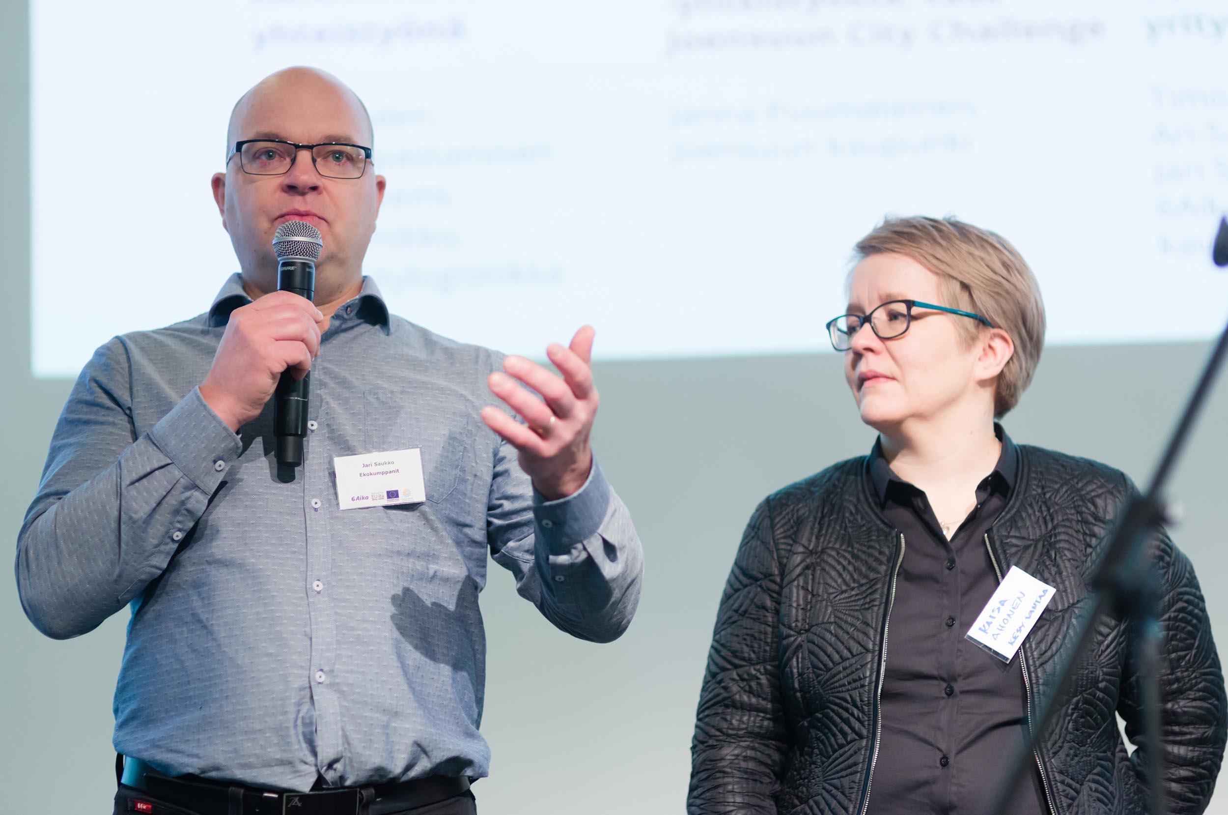 Mies ja nainen seisovat rinnakkain esiintymislavalla, mies puhuu mikrofoniin ja nainen kuuntelee.