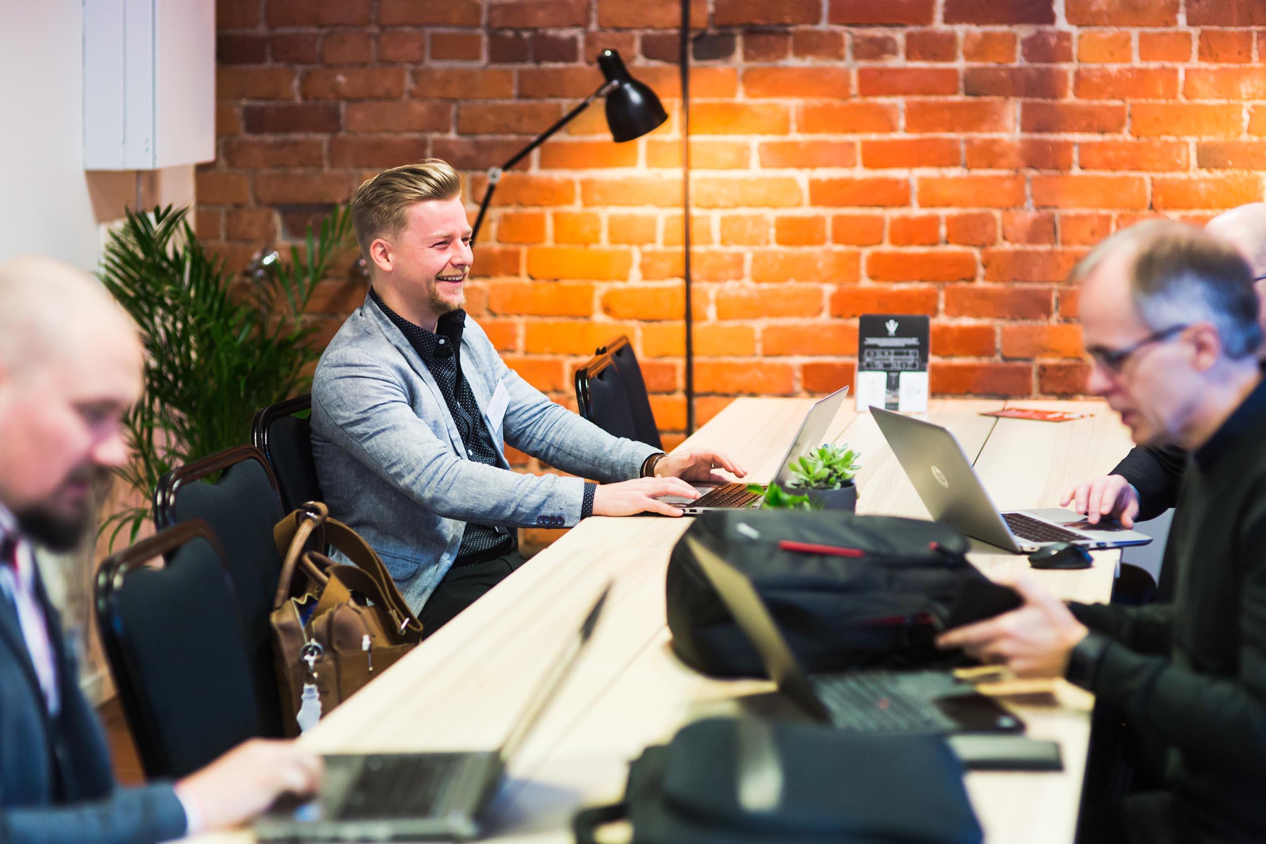 Miehiä pöydän ympärillä kokoustilassa, yksi miehistä nauraa. Taustalla tiiliseinä.