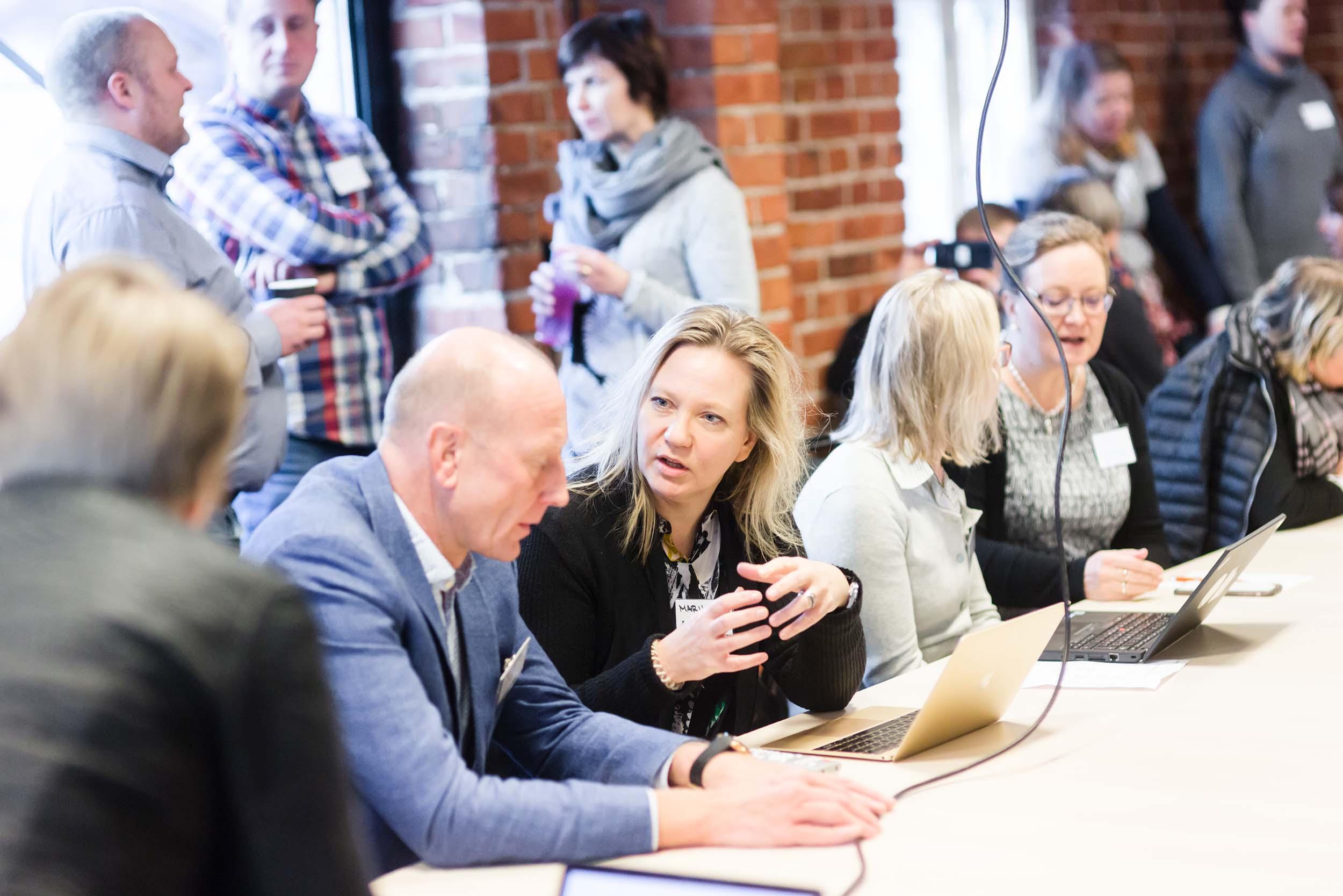 Ihmisiä, miehiä ja naisia kokoustilassa, keskustelevat pienryhmissä.