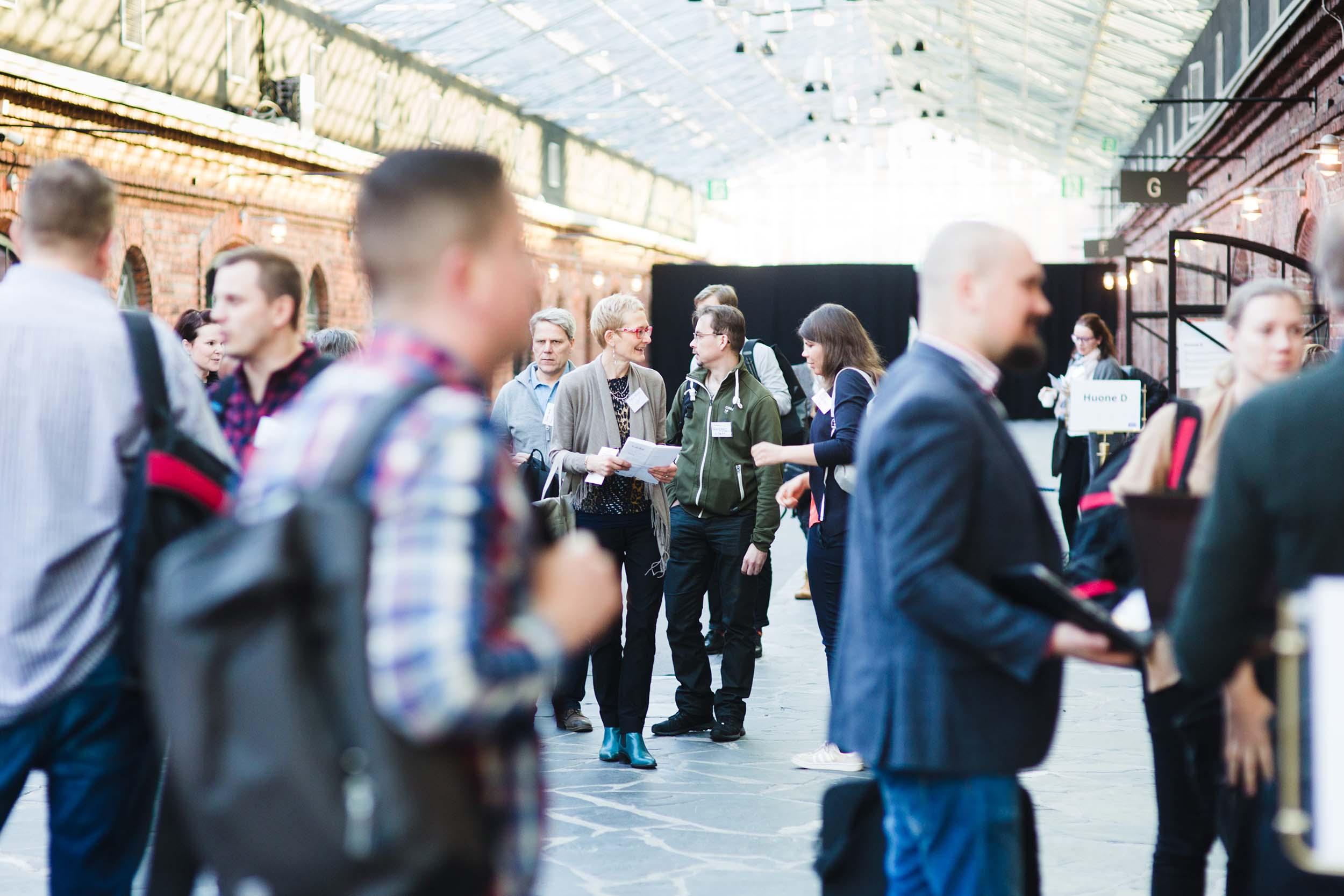 Paljon ihmisiä seminaaritilassa, miehiä ja naisia. Keskustelevat keskenään, osa liikkeellä. Tiiliseinät, lasikatto päästää valoa tilaan.