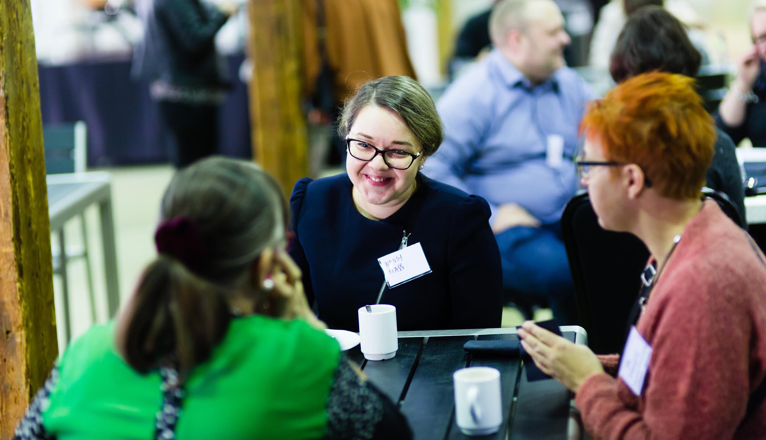 Kolme naista istuu pöydän ympärillä ja keskustelee, kasvot kameraan päin oleva nainen hymyilee.