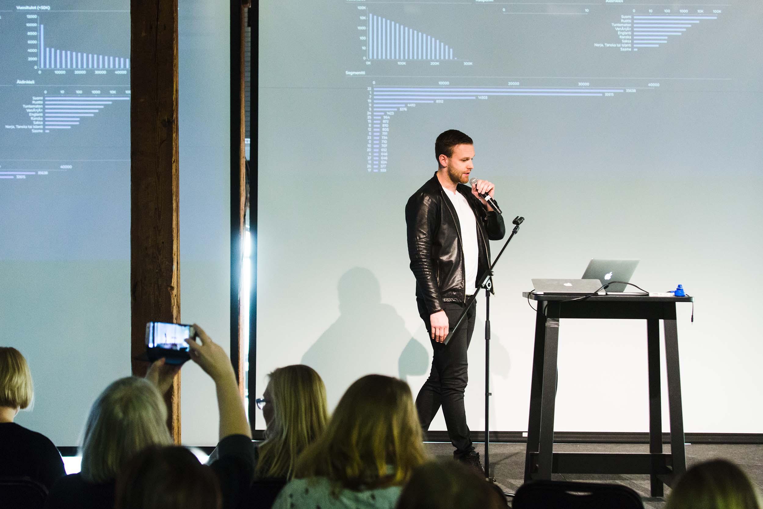 Nahkatakkinen mies puhuu mikrofoniin esiintymislavalla, taustalla esitys, jossa kaavioita.