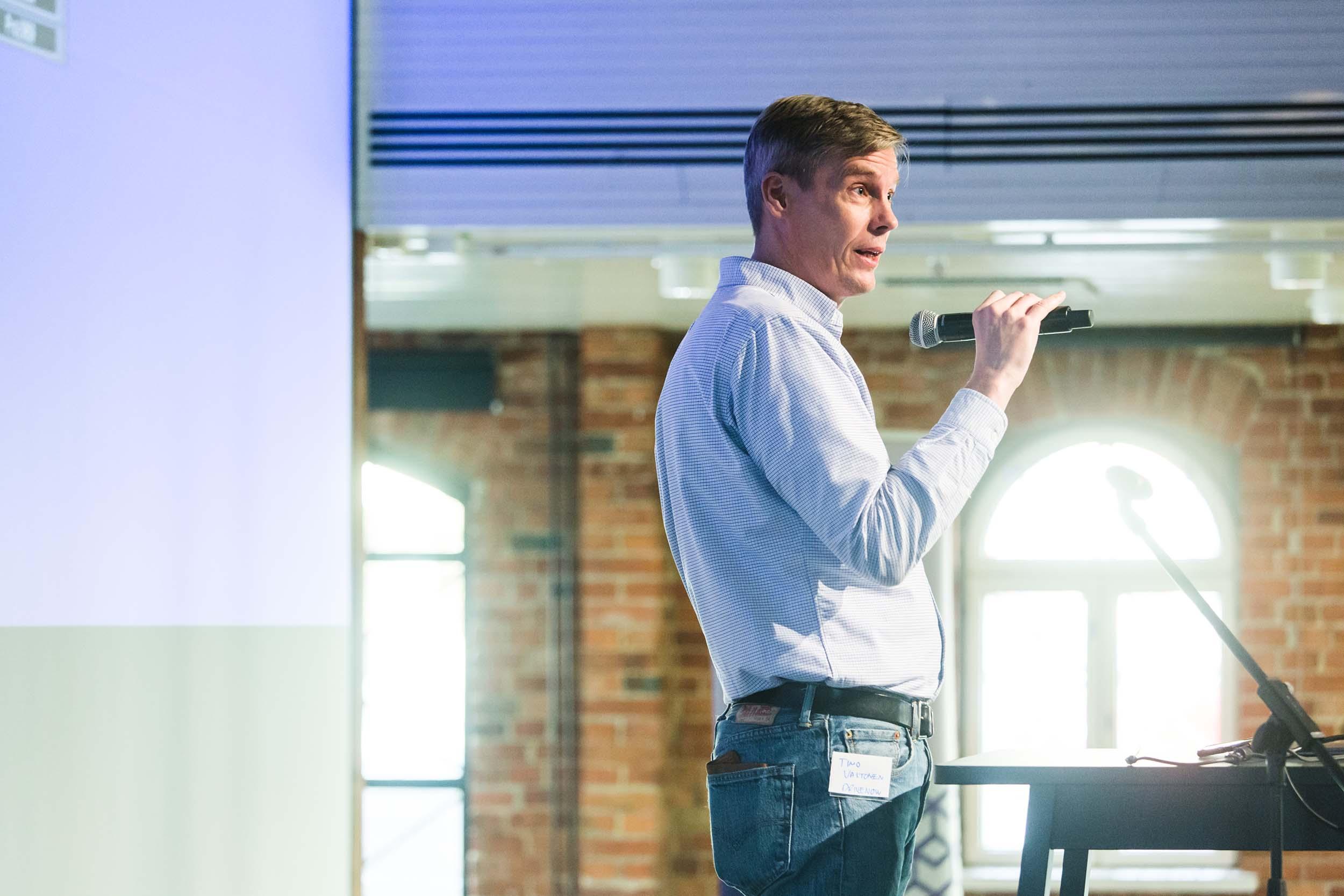 Mies puhuu esiintymislavalla mikrofoniin, taustalla tiiliseinä ja valoisat ikkunat.