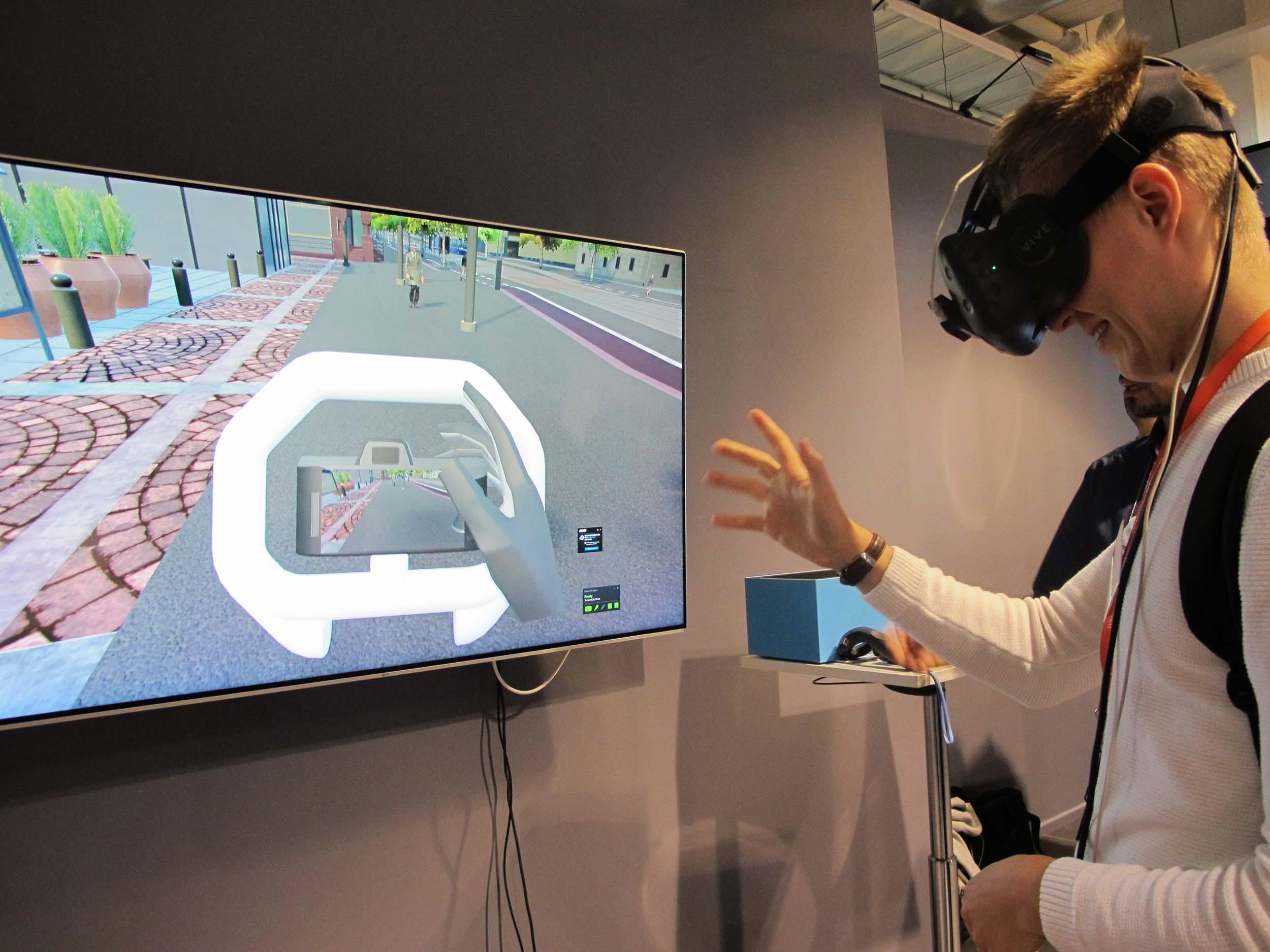 Mies seisoo VR-lasit päässä ruudun edessä, käsi ojentuneena, ruudulla katuympäristö.