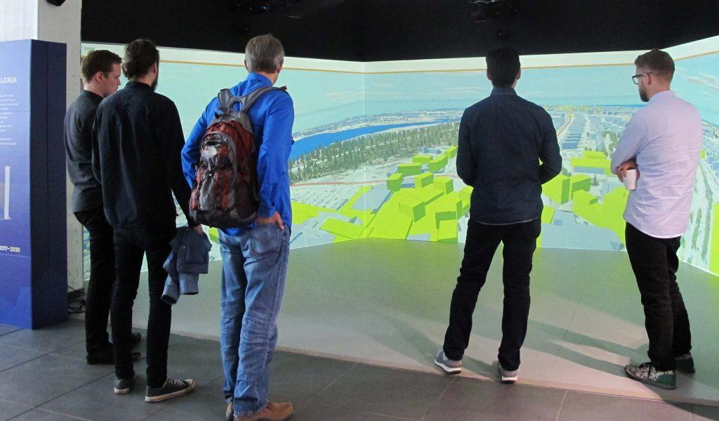Viisi miestä seisoo suuren ruudun edessä ja tarkastelee kaupunkimallia. Kuvattu takaviistosta.