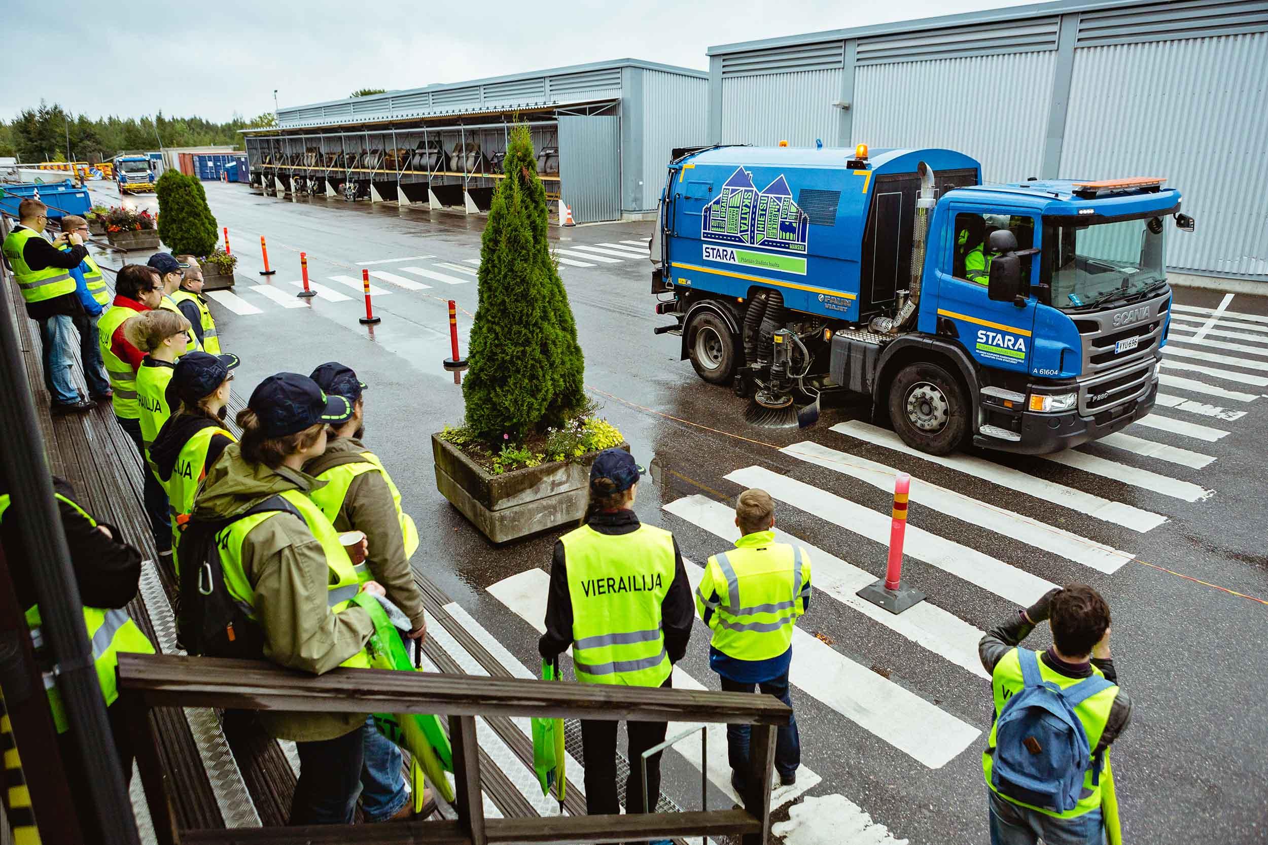 """Ryhmä ihmisiä seisoo ulkona ja tarkastelee sinistä kuorma-autoa, jossa kadunpuhdistusharjat. Kaikilla päällä keltaiset liivit, joissa lukee """"Vierailija""""."""
