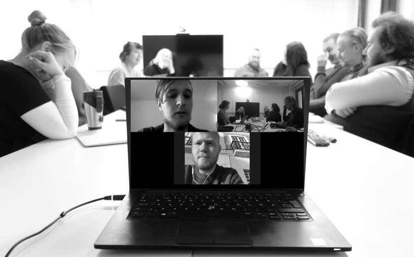 Miehiä ja naisia istuu pöydän ympärillä, etualalla laptop, jossa kokousohjelman kautta näkyy ihmisiä.