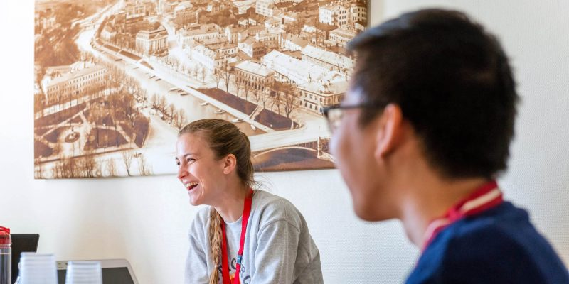 Nainen ja mies istuvat pöydän vieressä, nainen nauraa. Seinällä mustavalkoinen kuva kaupunkimaisemasta.