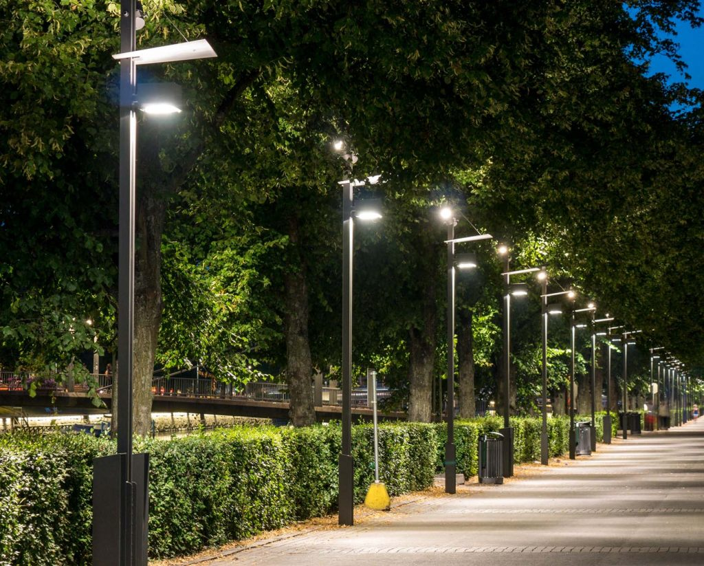 Katulamppuja rivissä valaistuina, ilta, vieressä vehreä puisto.