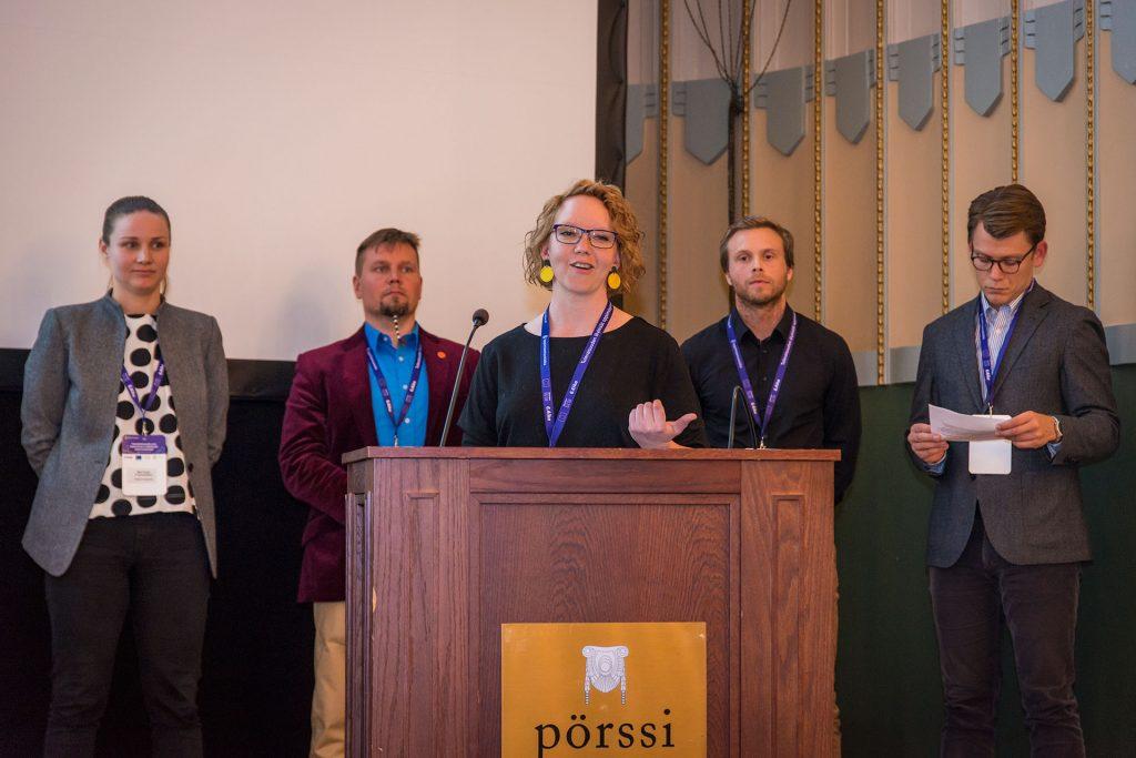 Viisi ihmistä, kaksi naista ja kolme miestä, seisoo seminaarisalin etuosassa. Toinen naisista puhuu mikrofoniin.
