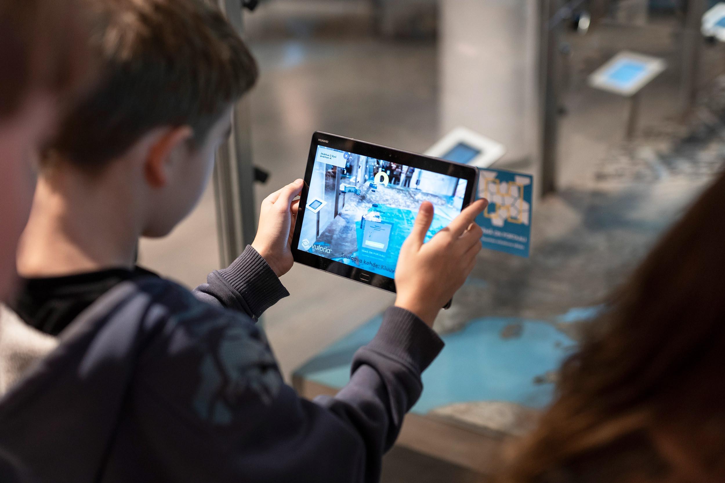 Koululainen (poika) osoittaa iPadia kaupungin pienoismallia kohti. Kuvattu takaviistosta.