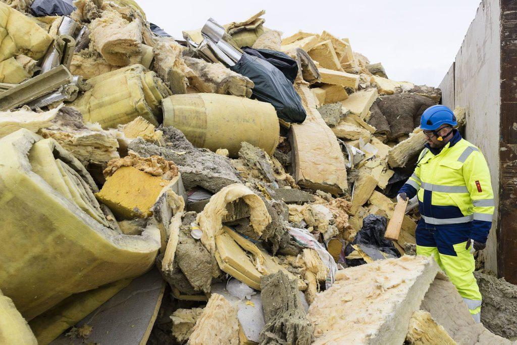 Mies suojavarusteissa seisoo suuren jätekasan vieressä, jäte koostuu eristevilloista