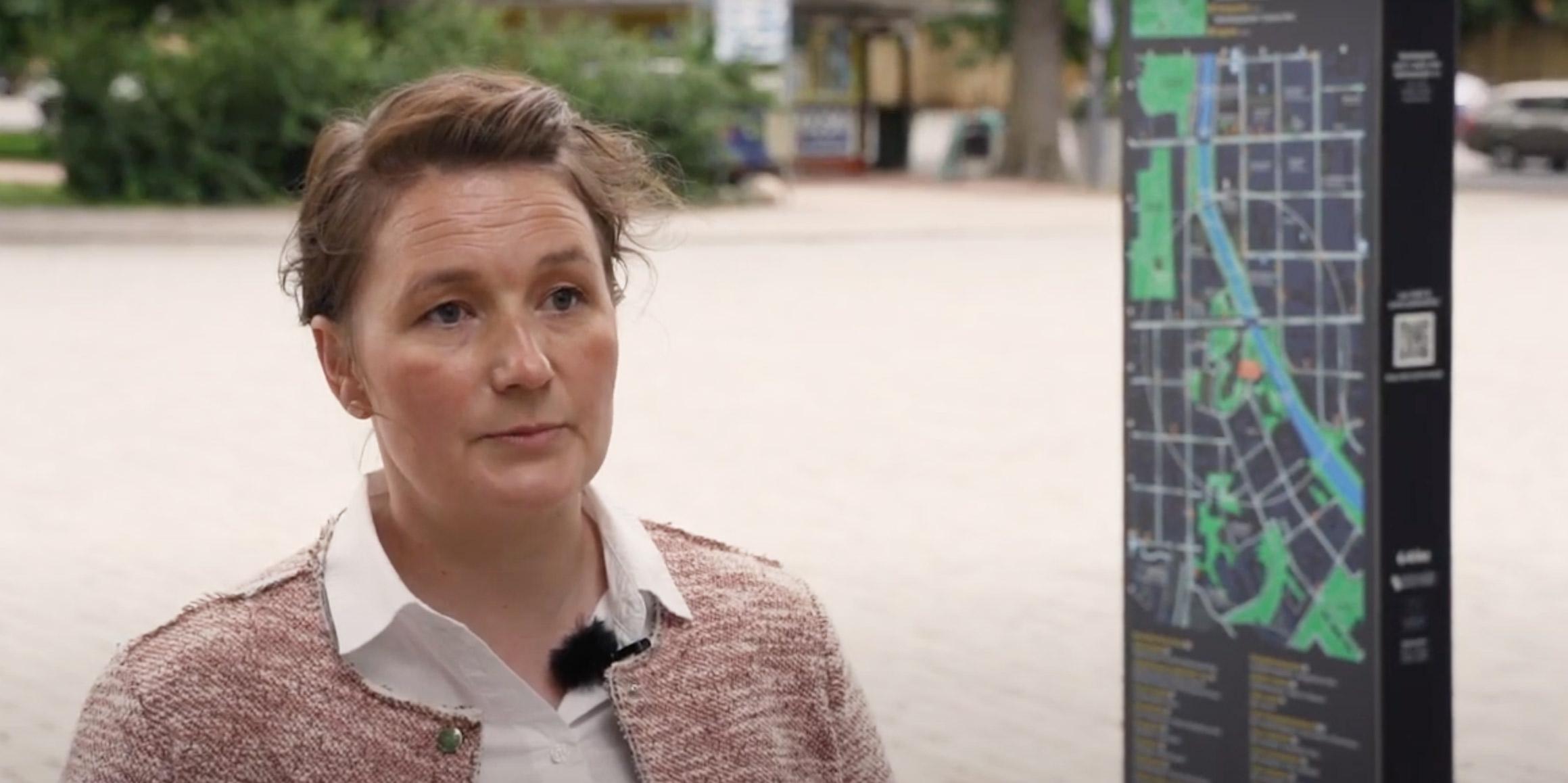 Nainen haastattelussa ulkona kadulla, taustalla näyttötaulu, jossa kaupungin karttanäkymä.