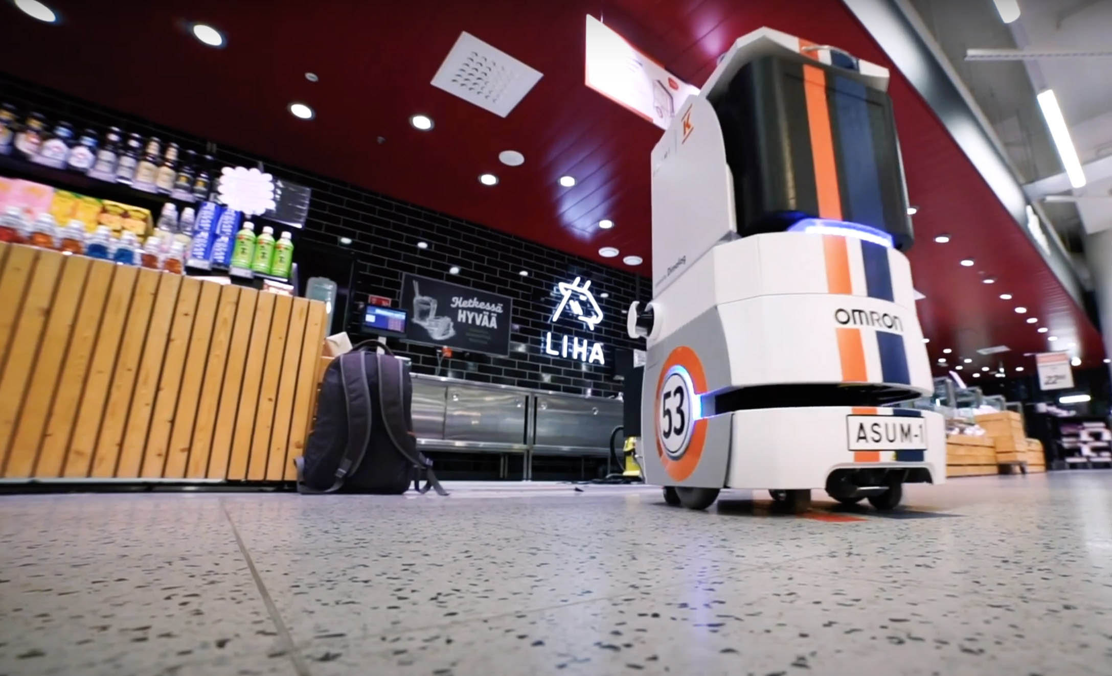 A small food delivery robot moving in a grocery store in REDI shopping centre