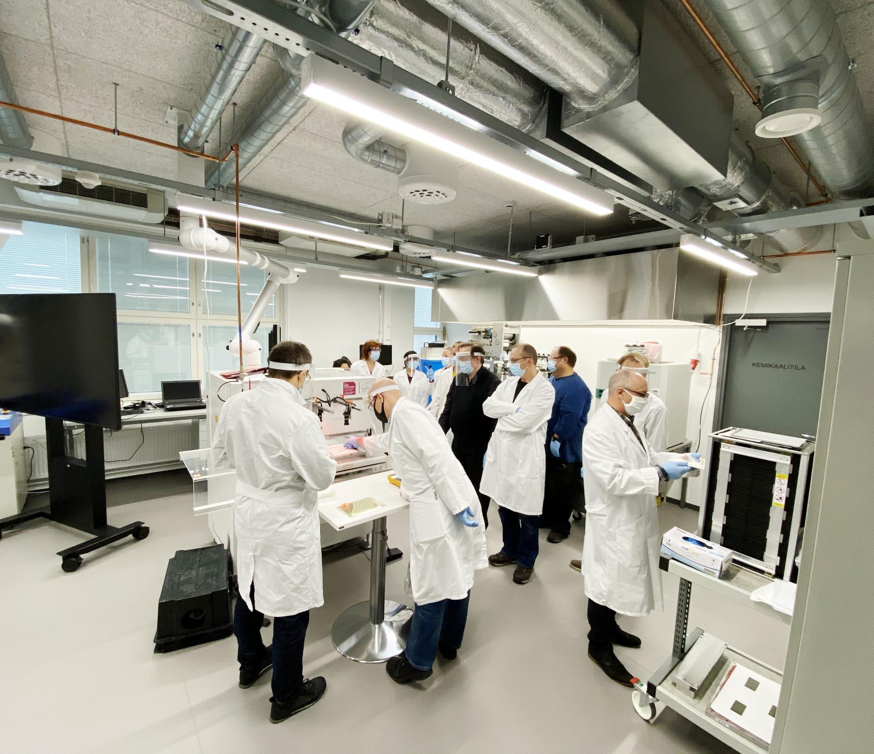 Ryhmä ihmisiä seisoo yhteisen pöydän ympärillä laboratoriossa, valkoiset takit ja kasvomaskit