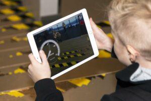 Lapsi pitelee tablettia käsissään, kuvattu takaviistosta. Tabletilla peli tai vastaava näkymä.