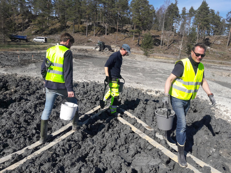 Three men walking on dredged soil, wearing rubber boots, carrying buckets.