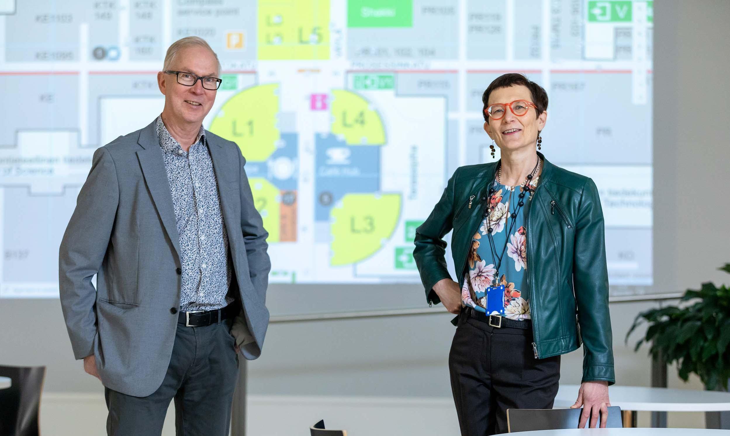 Mies ja nainen vihreässä lyhyessä nahkatakissa seisovat esitystilan edessä ja katsovat hymyillen kameraan. Taustalla esitys, jossa kaavioita.