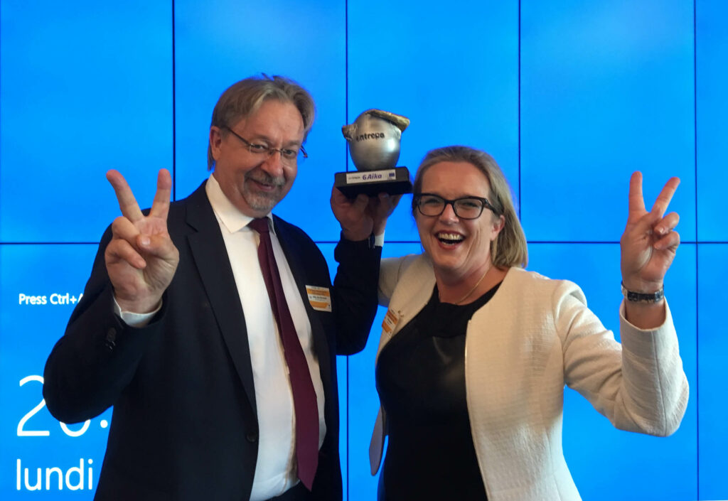 A man and a woman with a trophy, showing v sign.