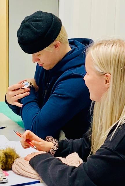 Opiskelijapoika katsoo kelloaan, vieressä istui opiskelijatyttö kynä kädessä, hymyilee.