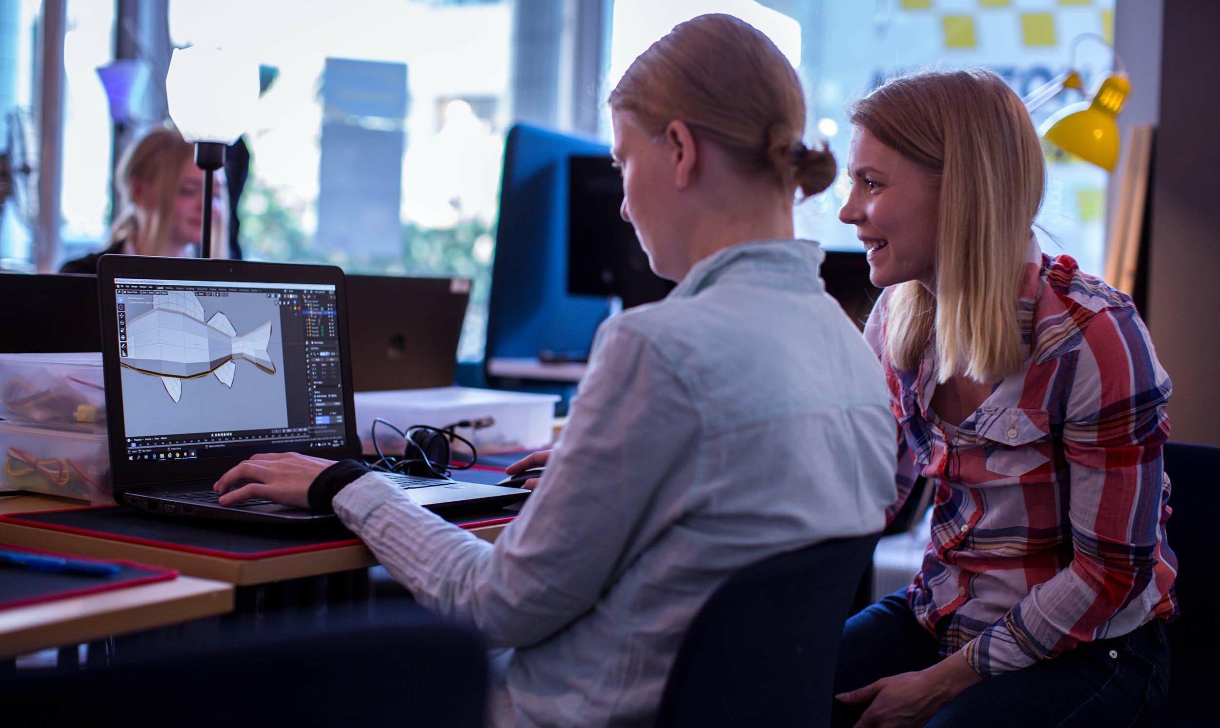 Tekstivastine: Kaksi nuorta naista istuu luokassa tietokoneruudun äärellä, työstävät piirto-ohjelmalla kalan kuvaa. Iloinen tunnelma.