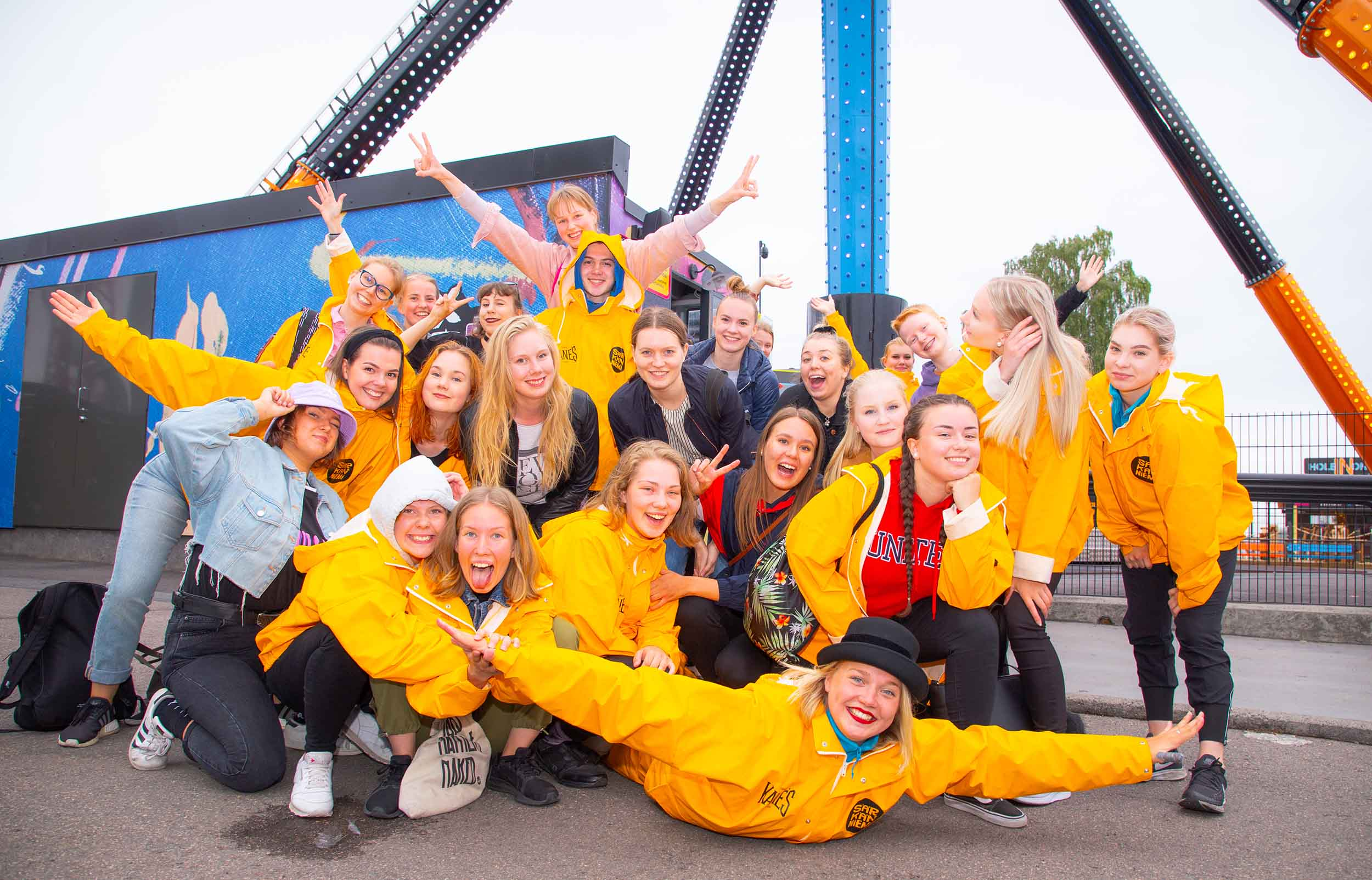 A large group of young women, many of whom are wearing a yellow jacket with the text 'Särkänniemi'. A happy atmosphere. Some have outstretched arms.