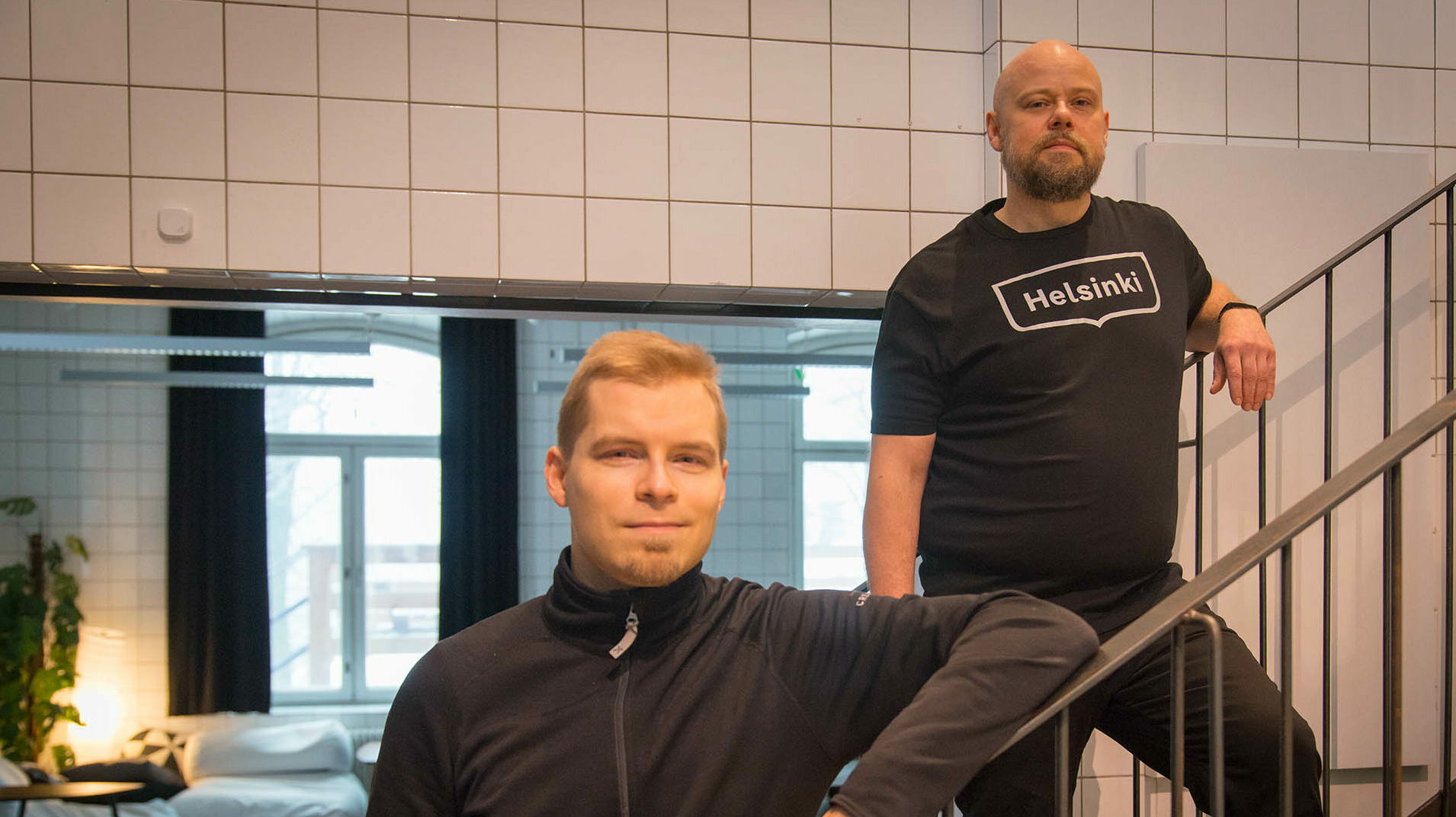 Kaksi miestä (Haila ja Sihvola) seisoo rinnakkain rappusilla, toinen alempana ja toinen ylempänä. Toisella on päällä t-paita, jonka rinnassa on Helsingin kaupungin logo.