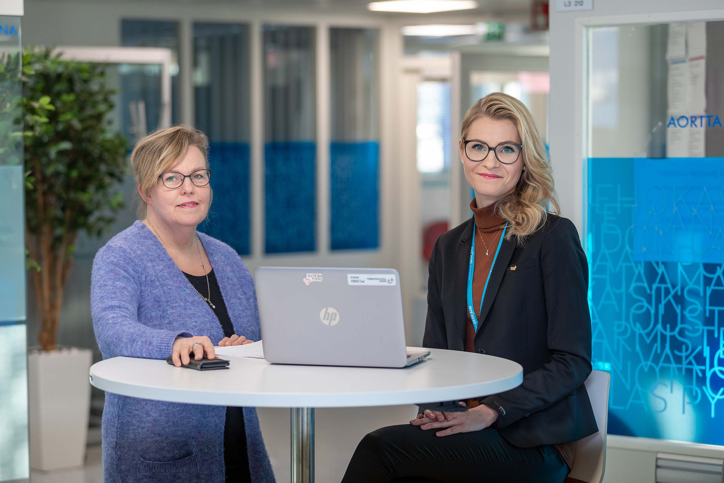 Kaksi naista poseeraa kameralle vierekkäin toimistotilassa, pystypöydän äärellä. Pöydällä on laptop kansi avoimena.