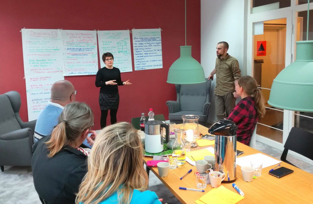 At a workshop. A woman is giving a presentation, and a man is standing next to her. The people around the table are listening to the woman. The wall in the background is red, and there are sheets of paper full of text on the wall.