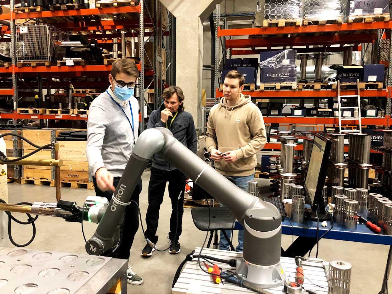 Kolme miestä tarkastelee robottia teollisuustilassa, robotissa on pitkä varsi.