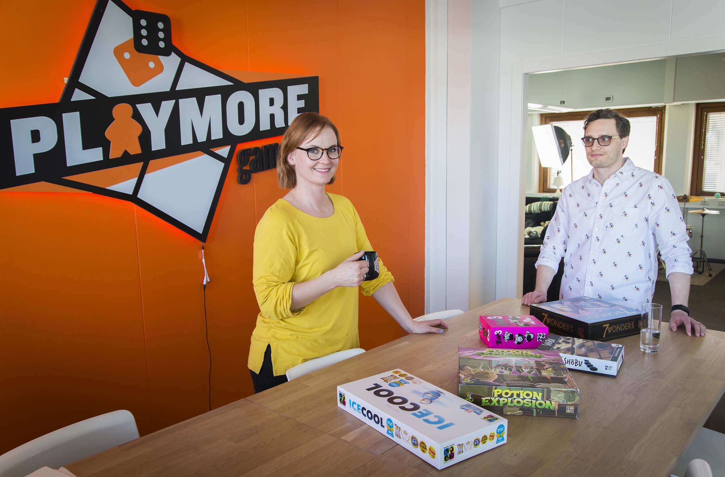 Nainen ja mies seisovat pöydän äärellä, nainen pitelee kahvikuppia. Pöydällä on lautapelejä, taustalla oranssi seinä, jossa lukee teksti