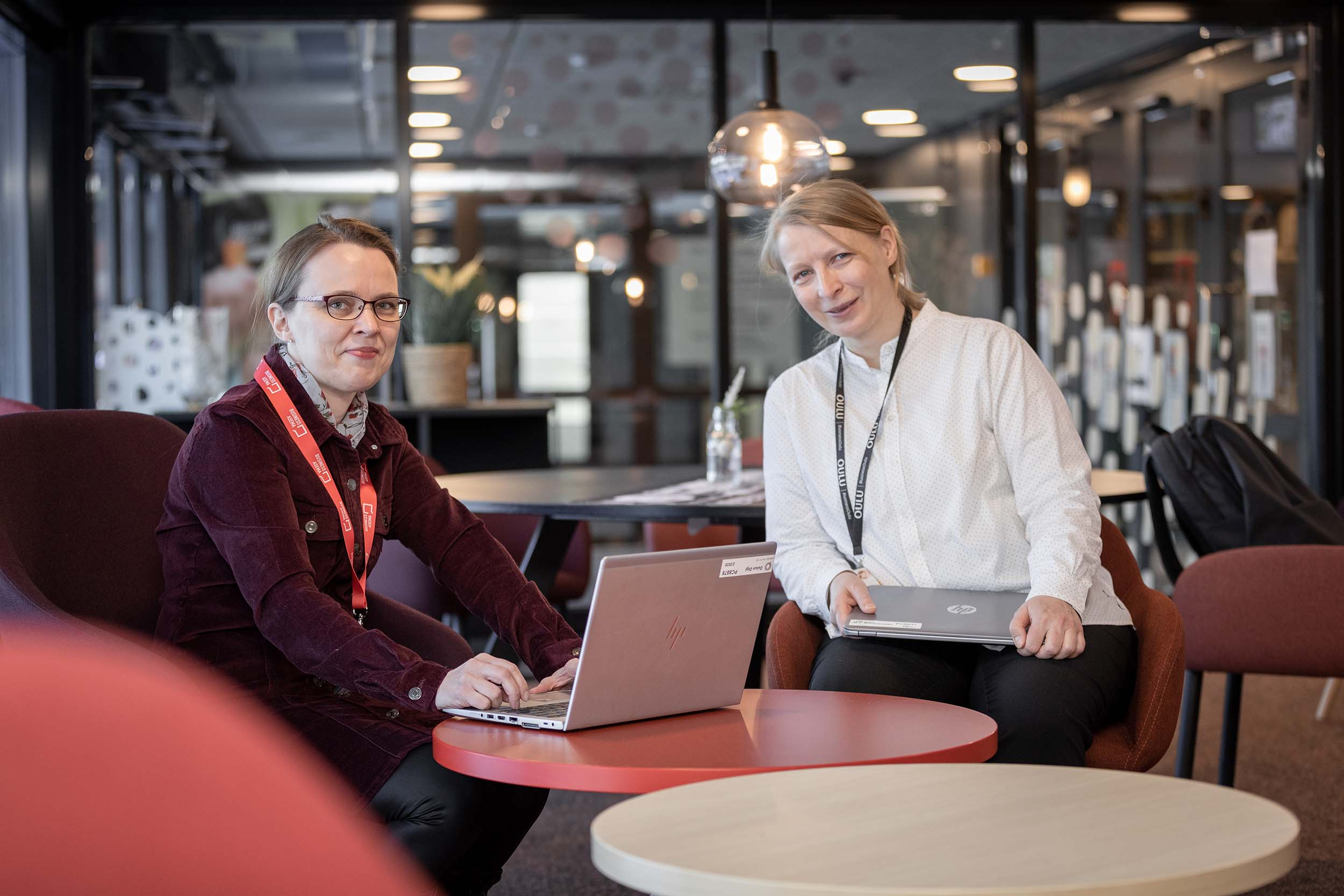 Kaksi naista istuu rinnakkain avotoimistoympäristössä ja poseeraa kameralle. Toinen ruskeahiuksinen, toinen vaalea.