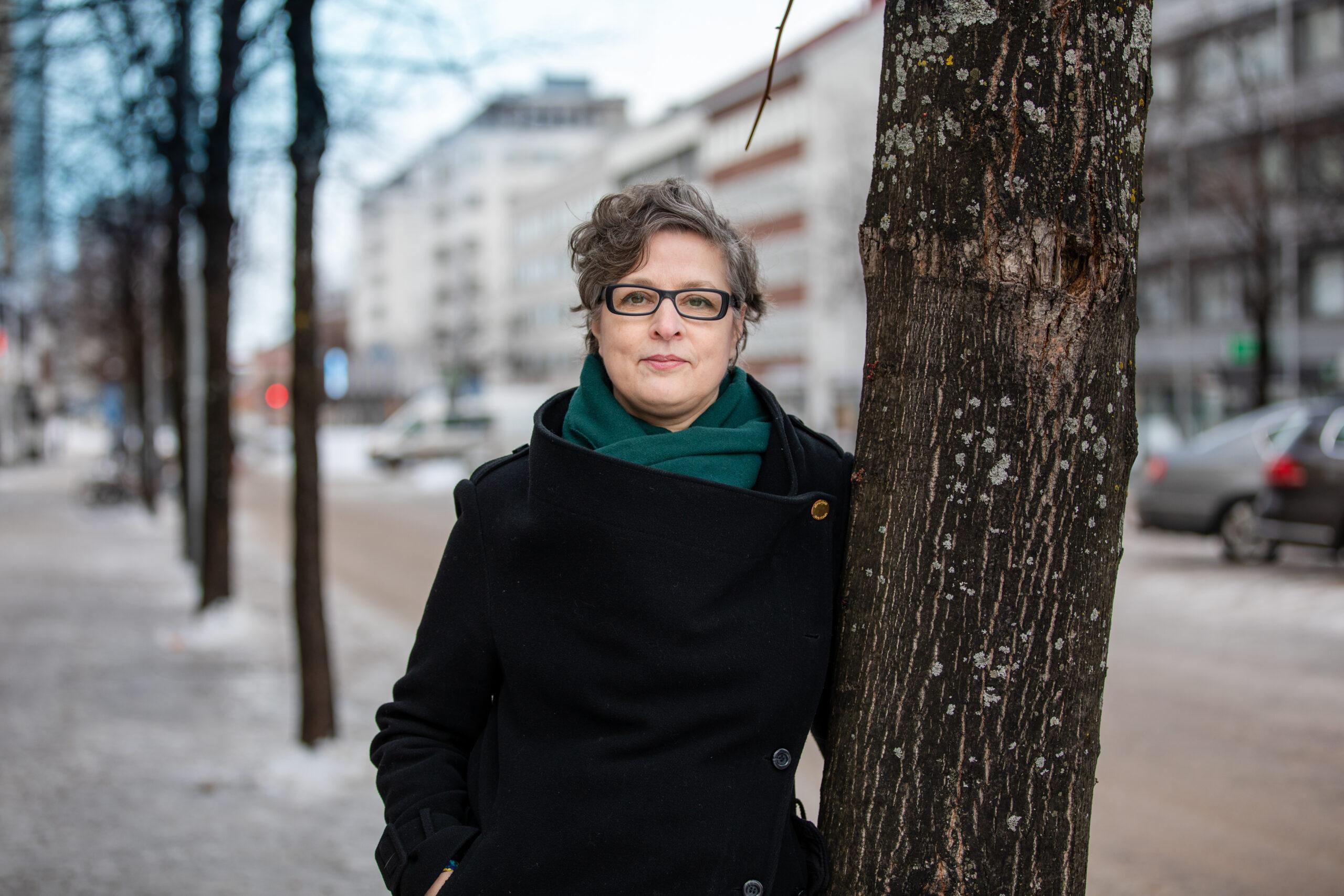 Nainen nojaa puuhun kaupunkinäkymässä