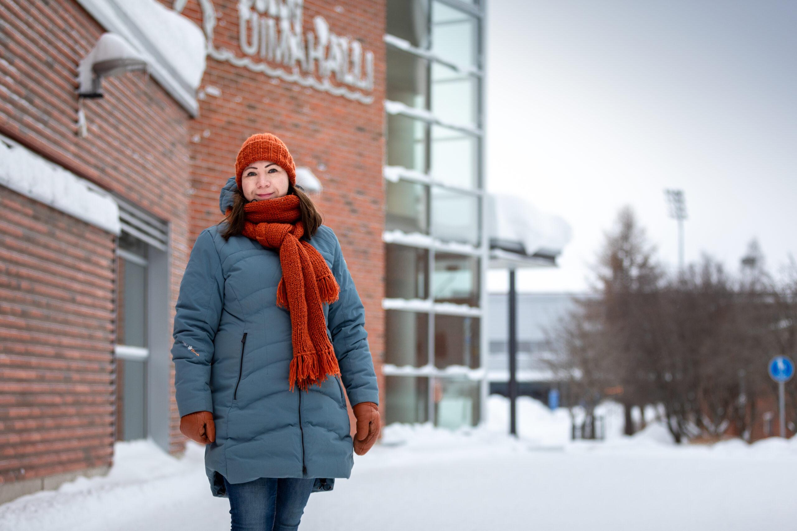 Kuvassa nainen seisoo punatiilisen rakennuksen edessä talvivaatteissa, maassa on lunta.