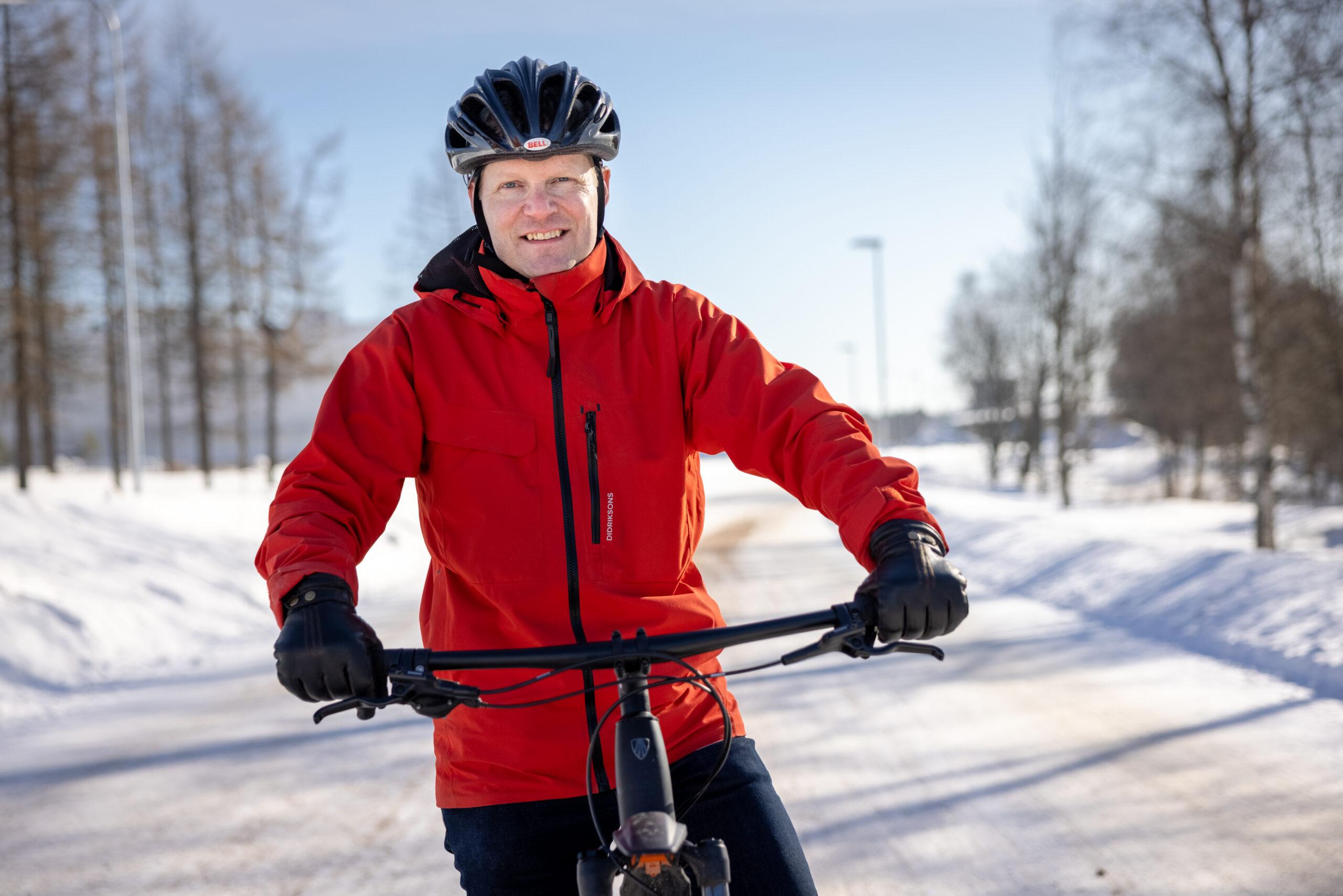 Mies poseeraa hymyillen talvisessa maisemassa pyörän kanssa ja kypärä päässä.