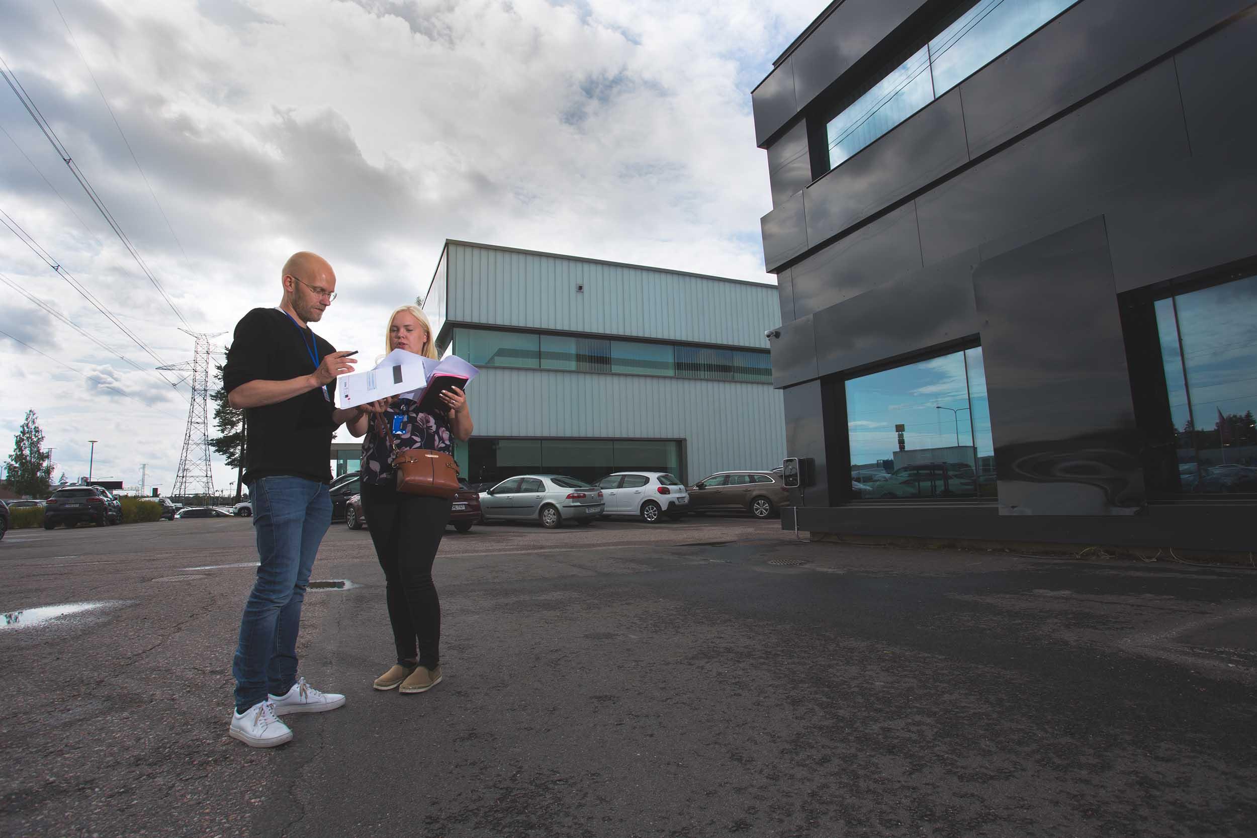 Mies ja nainen tarkastelevat papereita, seisovat teollisuusalueen pihassa, taustalla rakennuksia. Pilvinen päivä.
