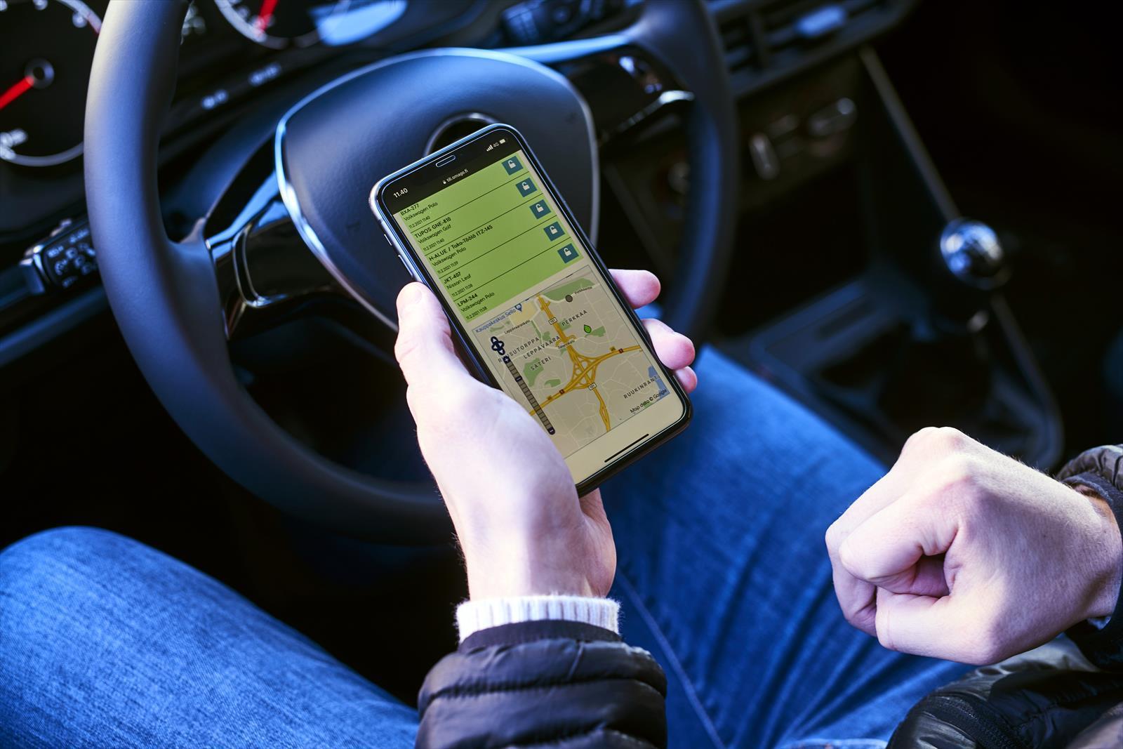 Kuvassa mies pitää kädessä puhelinta, jossa on auki liikennesovellus.