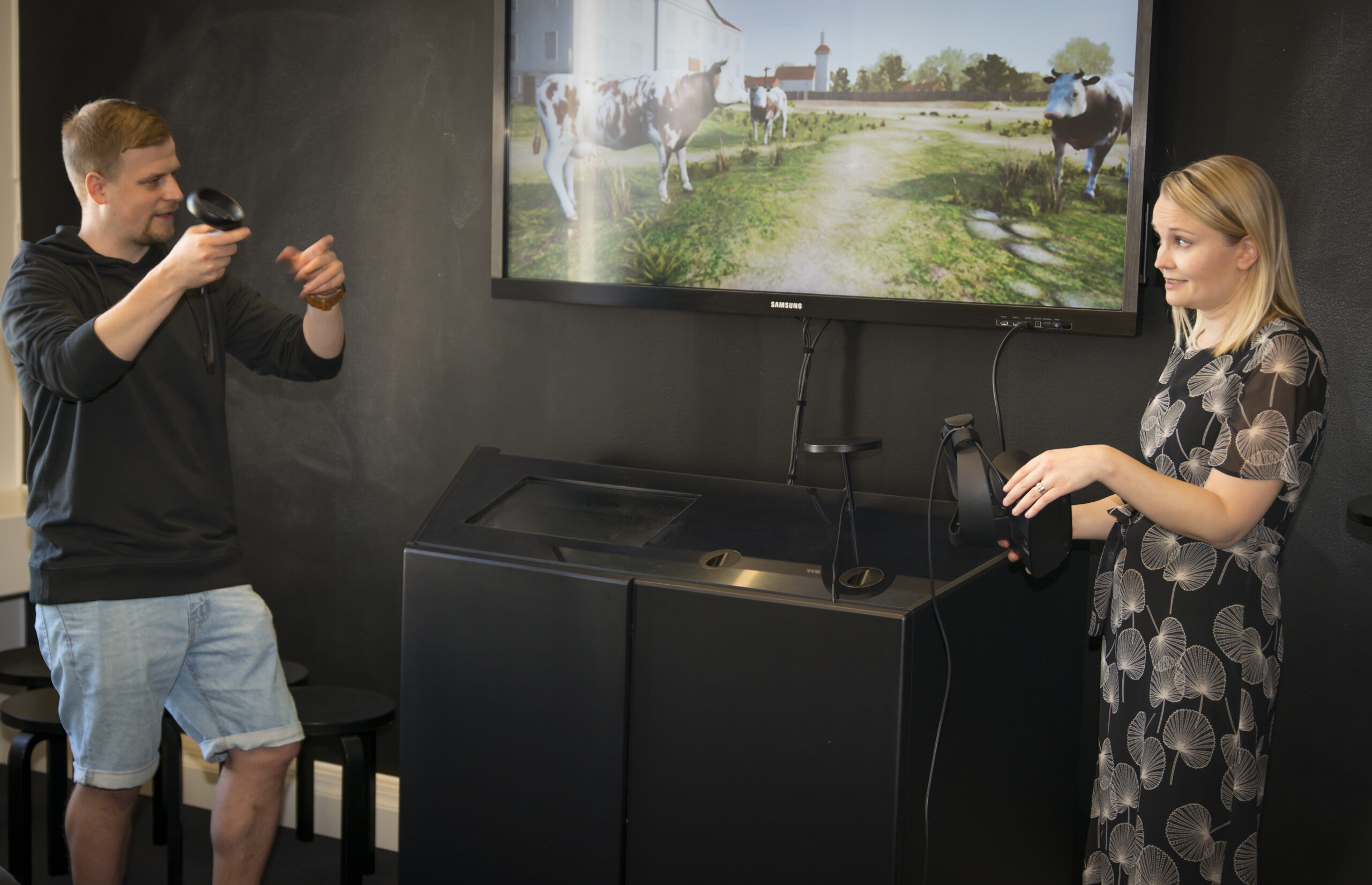Mies ja nainen seisovat ison näytön vierellä, naisella kädessä virtuaalitodellisuuslasit.
