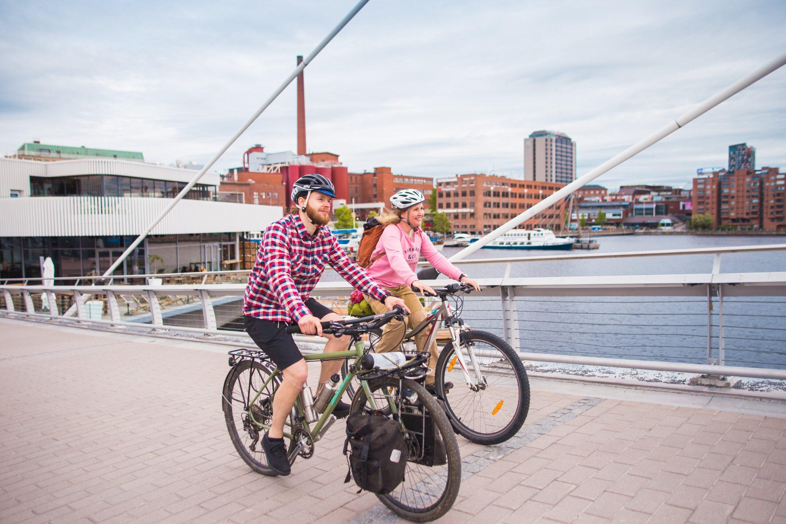 Mies ja nainen ajavat vierekkäin pyörillä sillalla Tampereen keskustassa.