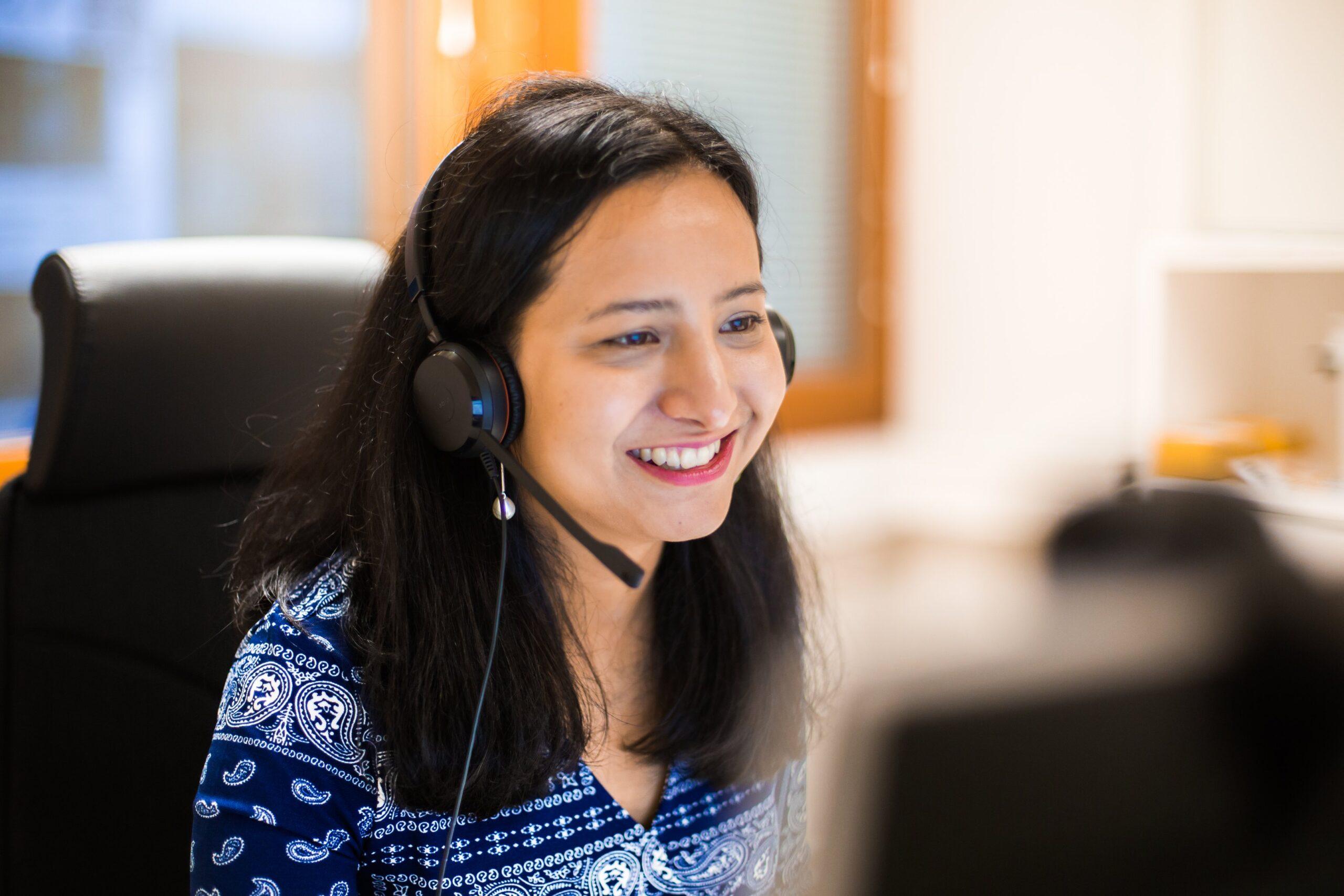 Nainen istuu työtuolissa, tietokoneen äärellä, kuulokesetti päässä.