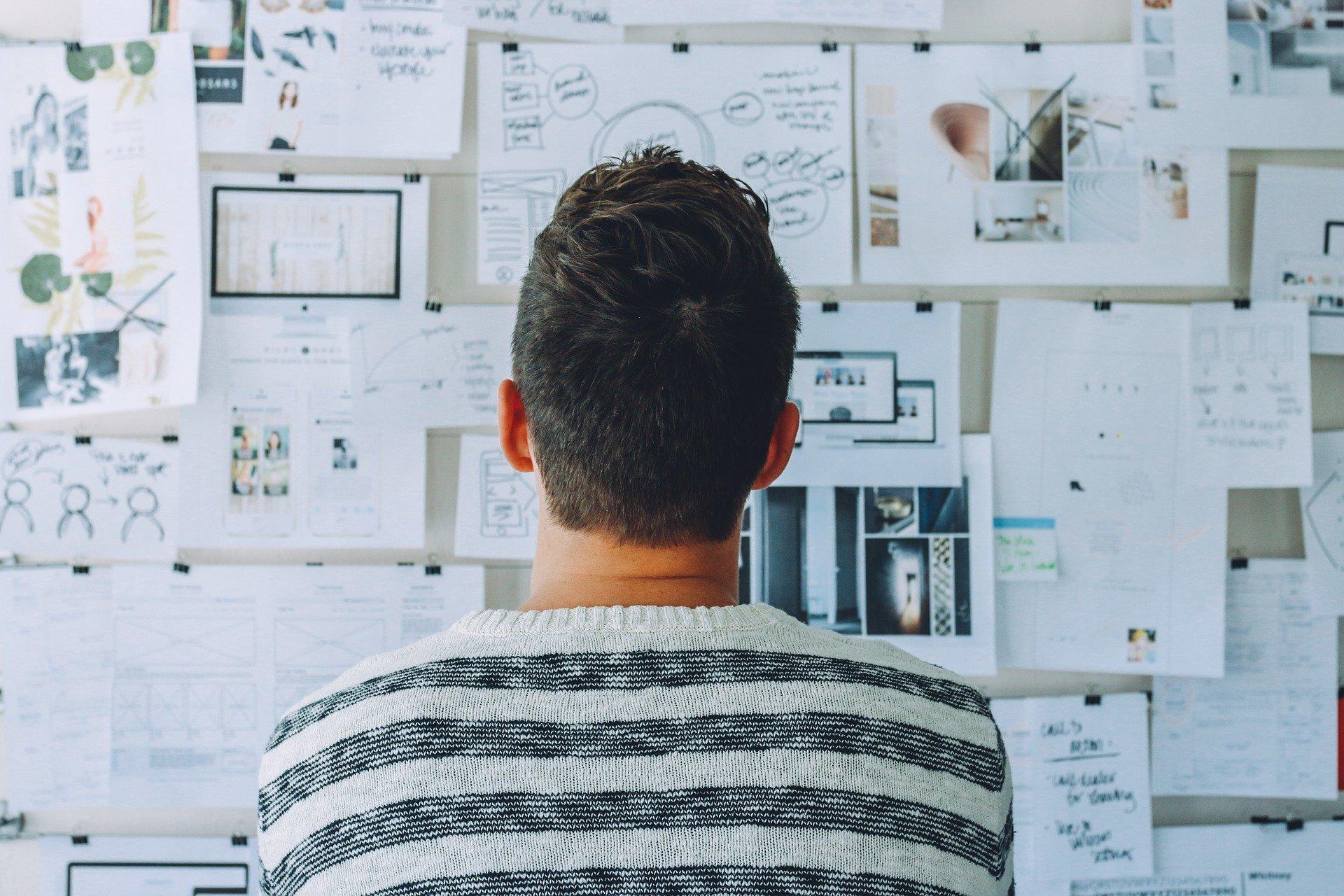 Kuvassa mies katselee seinää, jolla on suunnitelmia papereilla