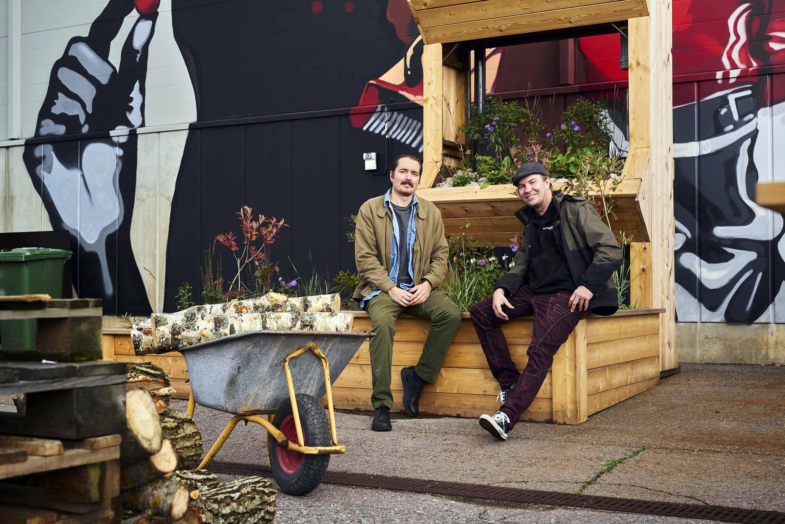 Kaksi miestä istuu puisen telineen edessä ja poseeraa kameralle. Telineellä kasvatetaan viherkasveja. Edessä kottikärryt.